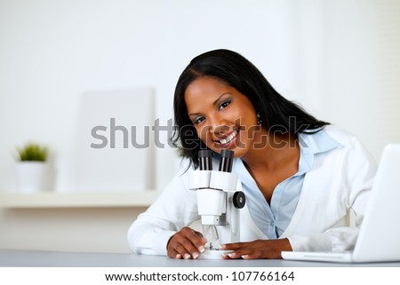 Portrait of a charming young female using a microscope while looking to you