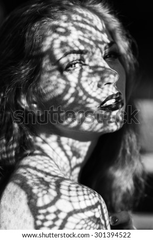 Portrait of a charming young woman outdoor. Light and shadow. interesting portrait of young girl\'s face covered with unusual shadow