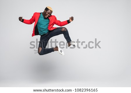 Portrait of a cheerful afro american man jumping isolated on a white background #1082396165
