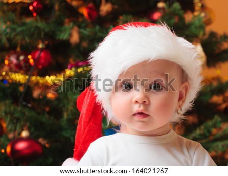 Portrait of a cheerful baby girl with Santa hat