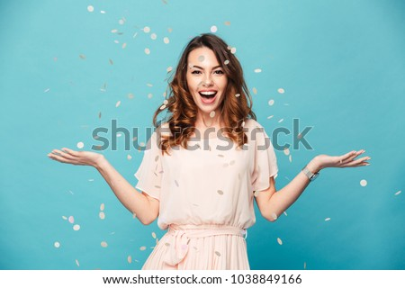 Photo of  Portrait of a cheerful beautiful girl wearing dress standing standing under confetti rain and celebrating isolated over blue background