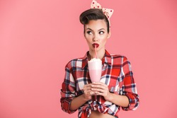 Portrait of a cheerful brunette pin-up girl in plaid shirt holding milk shake and looking away over pink background