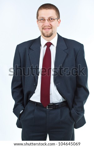 Portrait of a cheerful businessman in suit and tie, with glasses, hands in pockets, smiling confidently into camera - isolated on white