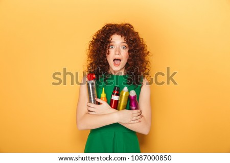Portrait of a cheerful curly redhead woman holding lots of hair care products isolated over yellow background