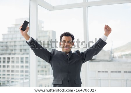 Portrait of a cheerful elegant young businessman cheering in a bright office