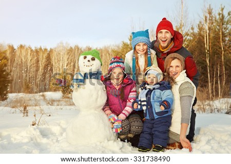 portrait of a cheerful family with snowman. happy children and parents in the winter outdoors #331738490