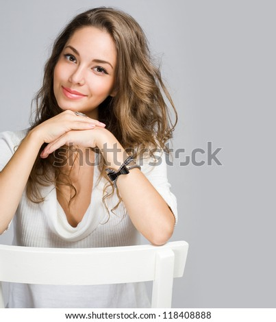 Portrait of a cheerful friendly young pensive brunette beauty.