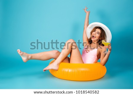 Portrait of a cheerful girl dressed in swimsuit sitting on inflatable ring and holding cocktail isolated over blue background #1018540582