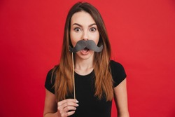 Portrait of a cheerful girl grimacing with fake moustaches isolated over pink background