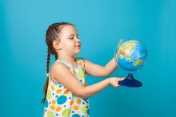 portrait of a cheerful girl in a white summer dress twirling a globe in her hand and choosing a country to travel, isolated on a blue background.