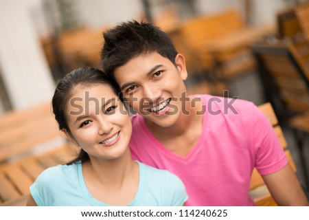 Portrait of a cheerful guy and girl smiling toothily at the camera - stock photo