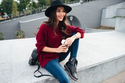 Portrait of a cheerful happy asian girl wearing hat and sweater holding coffee cup while sitting on a city street