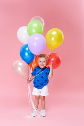 Portrait of a cheerful little toddler boy over pink background, holding bunch of colorful air balloons. The concept of children holiday birthday