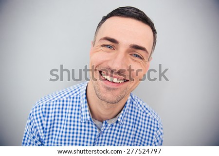 Portrait of a cheerful man looking at camera over gray background - Shutterstock ID 277524797