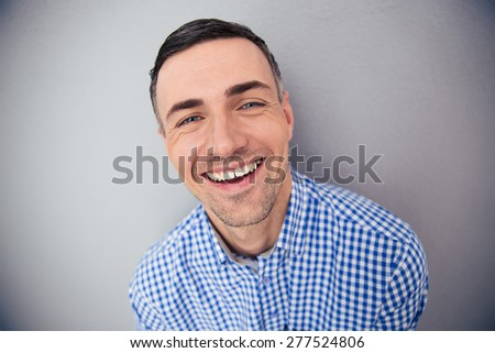 Portrait of a cheerful man looking at camera over gray background - Shutterstock ID 277524806