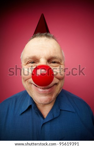 Portrait of a cheerful man with red nose smiling at camera on fool�s day - stock photo