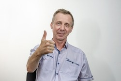 Portrait of a cheerful middle-aged man with bright blue eyes, raising his hand in a positive gesture meaning