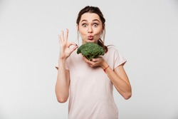 Portrait of a cheerful pretty girl holding broccoli and showing ok gesture isolated over white background