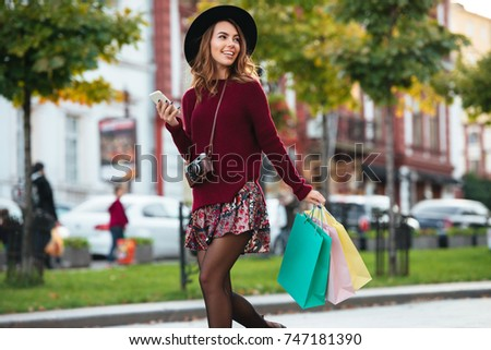 Portrait of a cheerful pretty girl with retro camera holding shopping bags and mobile phone while walking on a city street and looking away