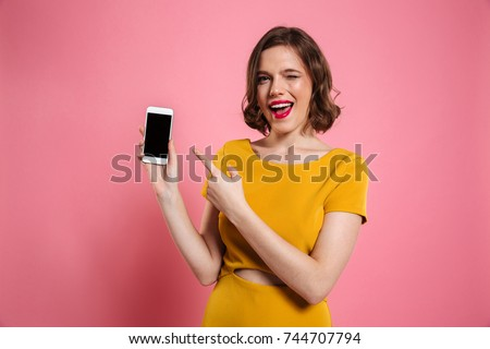 Portrait of a cheerful pretty woman pointing finger at blank mobile phone isolated over pink background