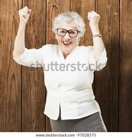 portrait of a cheerful senior woman gesturing victory against a wooden wall