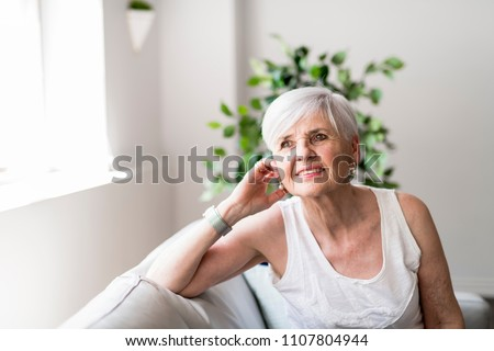 Portrait of a Cheerful senior Woman Sitting on the Sofa in the Living Room