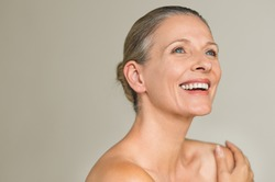 Portrait of a cheerful senior woman smiling while looking away isolated on gray background. Happy mature woman after spa massage and anti-aging treatment on face.