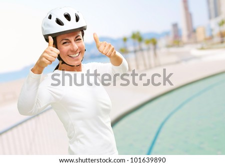 portrait of a cheerful sporty middle aged woman doing a victory symbol near the beach