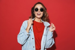 Portrait of a cheerful stylish young woman wearing denim jacket and sunglasses standing isolated over red background, posing