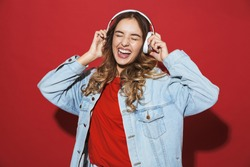 Portrait of a cheerful stylish young woman wearing denim jacket standing isolated over red background, listening to music with headphones, dancing