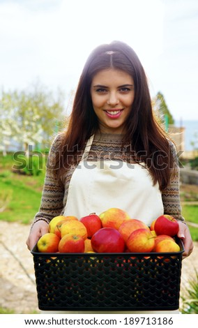Portrait of a cheerful woman holding basket with apples in garden