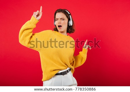Portrait of a cheerful woman in headphones listening to music and dancing isolated over pink background