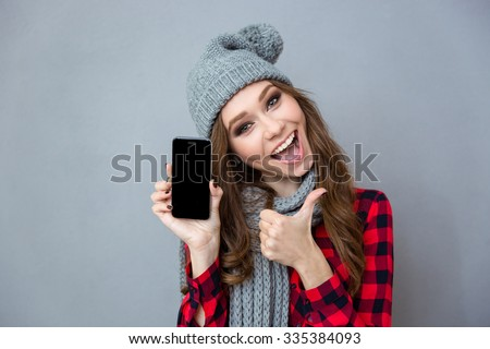 Portrait of a cheerful woman showing blank smartphone screen and thumb up over gray background