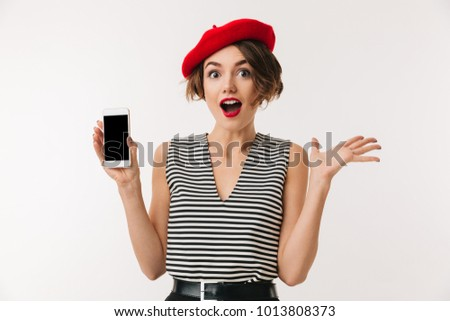 Portrait of a cheerful woman wearing red beret showing blank screen mobile phone isolated over white background