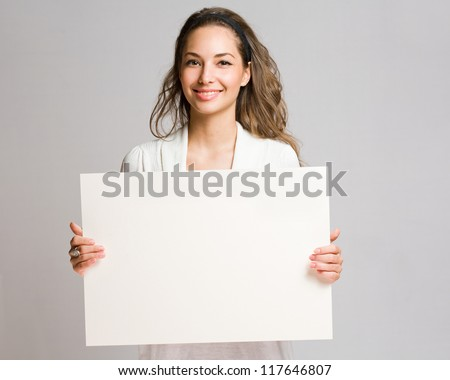 Portrait of a cheerful young brunette woman holding a white blank banner.