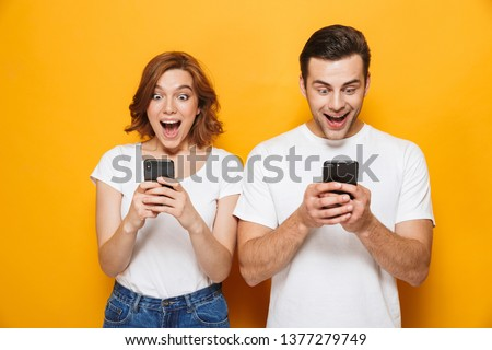 Portrait of a cheerful young couple standing isolated over yellow background, using mobile phones #1377279749