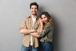 Portrait of a cheerful young couple standing together isolated over gray background, hugging