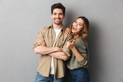 Portrait of a cheerful young couple standing together isolated over gray background, showing thumbs up