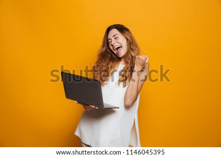 Portrait of a cheerful young girl holding laptop computer and celebrating success isolated over yellow background #1146045395
