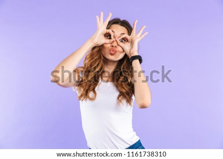 Portrait of a cheerful young girl standing isolated over violet background, showing ok gesture #1161738310