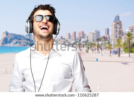 portrait of a cheerful young man listening music against a beach