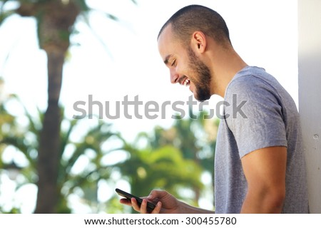 Portrait of a cheerful young man reading text message on mobile phone