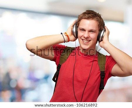 portrait of a cheerful young student listening to music with headphones indoor