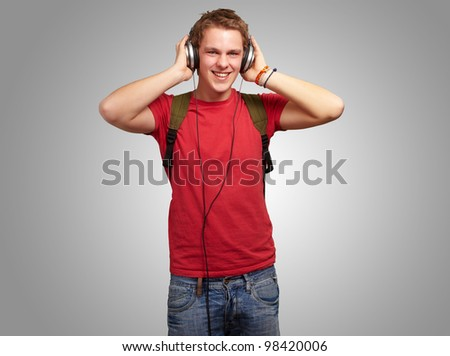 portrait of a cheerful young student listening to music with headphones over a grey background