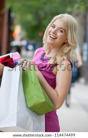 Portrait of a cheerful young woman carrying shopping bags