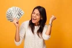 Portrait of a cheerful young woman holding money banknotes and celebrating isolated over yellow background