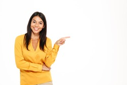 Portrait of a cheerful young woman pointing finger away at copy space isolated over white background