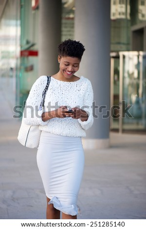 Portrait of a cheerful young woman walking on sidewalk and sending text message on mobile phone