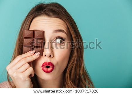 Portrait of a cheery brown haired woman with bright makeup holding chocolate bar at her face isolated over blue background