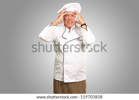 Portrait Of A Chef Having Headache Isolated On gray Background